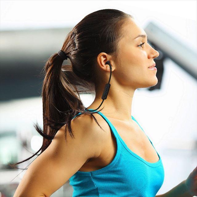 Bluetoothイヤホンをつけてランニングする女性の画像1