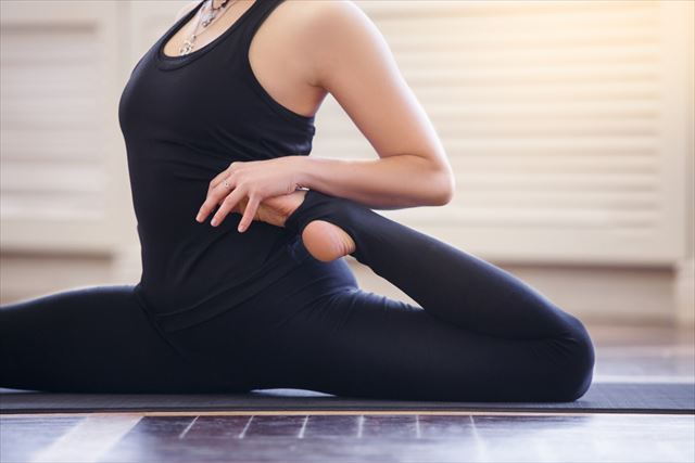 ホットヨガで関節に無理のある動きをする女性の画像