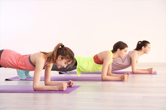 肘と膝に体重のかかるヨガポーズをする女性の画像