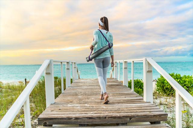 軽量のヨガマットを持ち運ぶ女性の画像