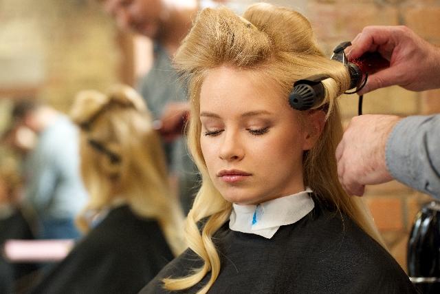 ヘアアイロンで髪をセットされている女性の画像