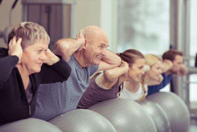 バランスボールで筋トレする高齢者の画像