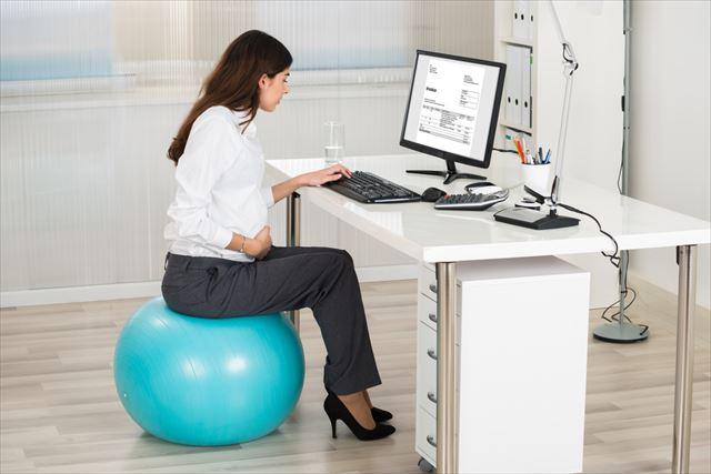 パソコンで仕事しながらバランスボールに乗る女性の画像