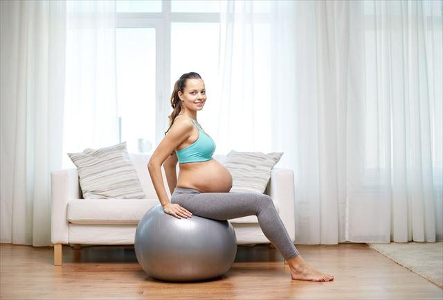 妊婦の女性がバランスボールに乗った画像