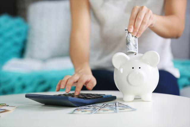 お金を貯金箱に貯める女性の画像