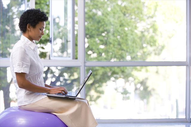 バランスボールに乗りながらパソコンをチェックする女性の画像