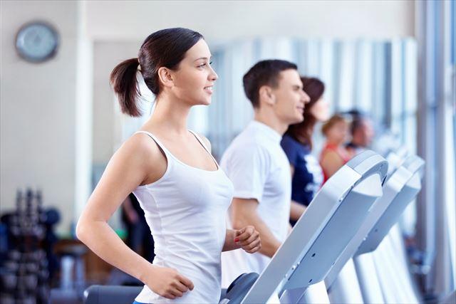 ランニングマシンでトレーニングする女性の画像