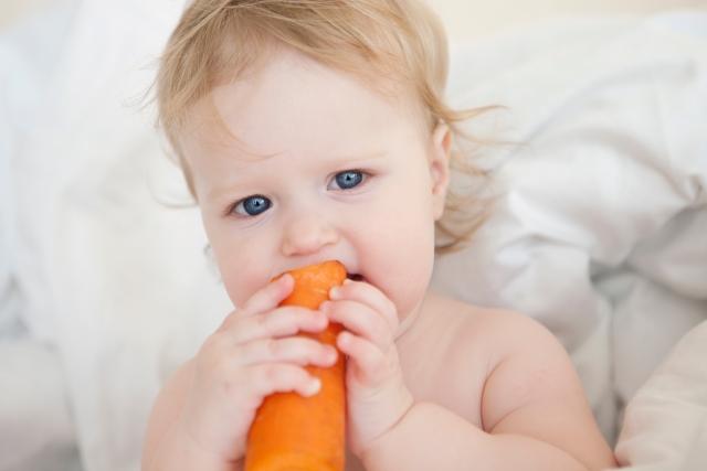 野菜をかじる赤ちゃんの画像