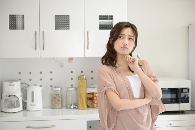 台所で悩む女性の画像