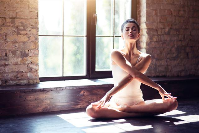 ヨガポーズで精神を集中する女性の画像
