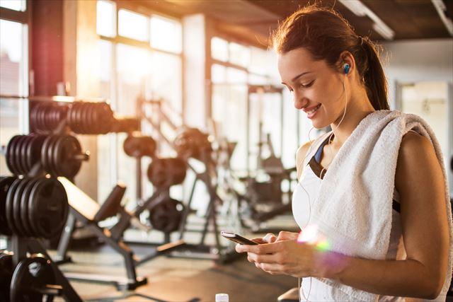 トレーニングジムでアイフォンを見る女性の画像