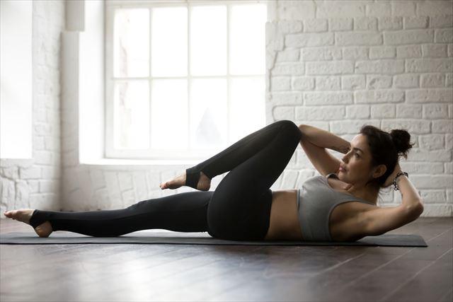自宅で腹筋運動する女性の画像