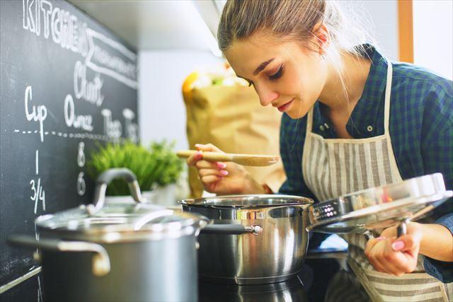 キッチンでたくさんの料理を作る女性の画像
