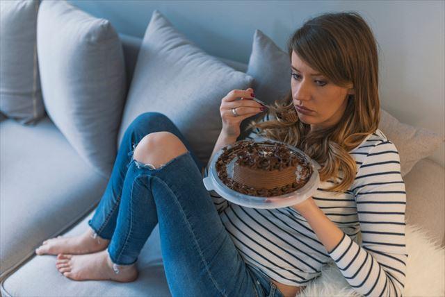 夜にケーキを食べる女性の画像