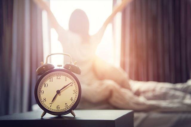 ベッドで目覚めた女性の画像