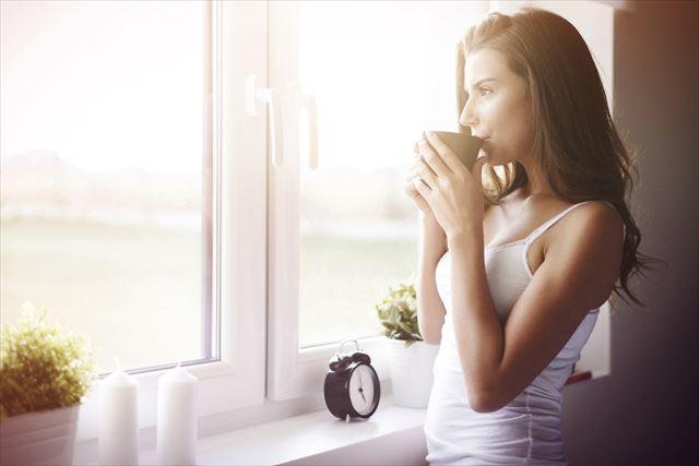 朝日を浴びながらコーヒーを飲む女性の画像
