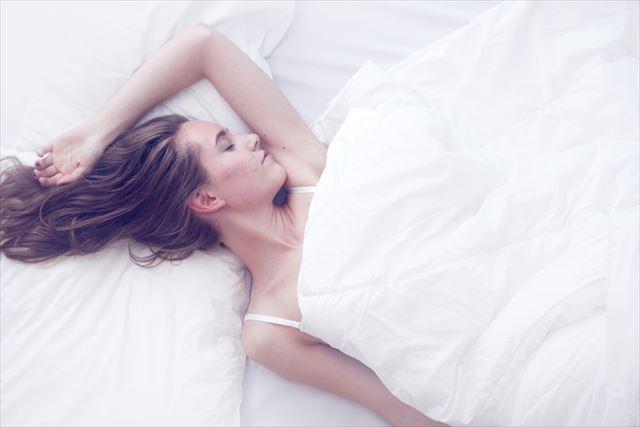 ベッドでぐっすり眠る女性の画像